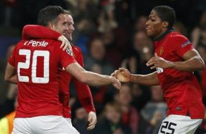 Manchester United's Robin van Persie, Rooney and Valencia celebrate a second goal against Olympiakos during their Champions League soccer match in Manchester