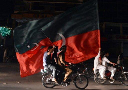 Supporters of Imran Khan carry their party flags as they take part in a rally in Rawalpindi, Pakistan on May 12, 2013