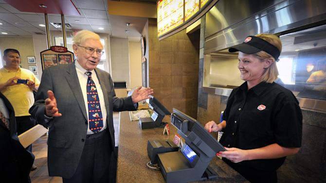 "IMAGE DISTRIBUTED FOR DAIRY QUEEN - Berkshire Hathaway's Warren Buffett orders lunch from Kathy White on Monday, May 20, 2013 in Omaha, Neb. Buffet helped launch the ""The First S'mores Blizzard of Summer"" and was celebrated as Dairy Queen's number one fan. (Dave Weaver/AP Images for Dairy Queen)"
