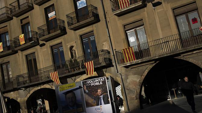 """In this photo taken on Saturday, Nov. 10, 2012, an electoral poster of the leader of center-right Catalan Nationalist Coalition (CiU) Artur Mas is seen next to balconies adorned with pro-independence """"estelada"""" flags and also """"senyeras"""" Catalan flags in Vic, a town declared by the city council a """"free Catalan territory"""" in Spain. Catalonia holds elections on Sunday that will be seen as a test of the regional government's plans to hold a referendum on independence, and one of the key issues emerging is the theoretical place of a free Catalonia in Europe. (AP Photo/Emilio Morenatti)"""