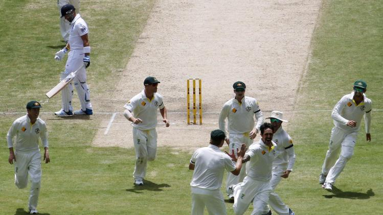Australia's Johnson celebrates with teammates after taking the wicket of England's Prior during the third day's play in the second Ashes cricket test at the Adelaide Oval