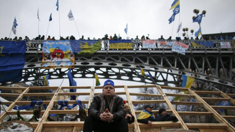 A man sits on a barricade during a rally organized by supporters of EU integration in central Kiev