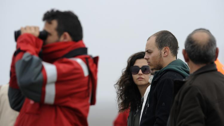 Friends and relatives stand next to a Red Cross member searching the area where a Portuguese-flagged fishing boat, the Santa Ana, sank with nine crew members onboard in Gozon, off Cape Pena