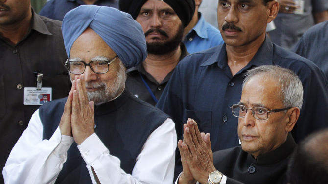 India's President elect Pranab Mukherjee, right,  and Indian Prime Minister Manmohan Singh, greet the media outside Mukherjee's residence in New Delhi, India, Sunday, July 22, 2012. The candidate from India's governing Congress party, former Finance Minister Pranab Mukherjee, was declared winner Sunday in the election for the country's next president, a largely ceremonial position.  (AP Photo/ Manish Swarup)