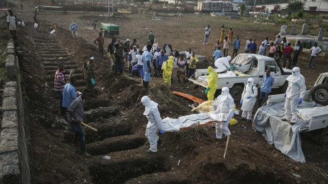 Health workers carry the body of an Ebola victim for burial at a cemetery in Freetown