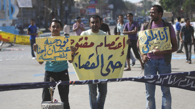 "Demonstrators hold banners with arabic words that reads "" Open strike there is retribution"" center, "" I'm a thug"" ridiculing official accusations that protesters are violent thugs, right, and "" Revolutionaries but they call us thugs."" left, as they protest in the Martyrs Square in Suez, Egypt, Tuesday, July 5, 2011. Hundreds of Egyptians attacked a courtroom in Cairo Monday, scuffled with security guards, and blocked a major highway for hours after the court ordered the release of 10 policemen charged with killing protesters in Suez during the country's uprising.(AP Photo/Khalil Hamra)"