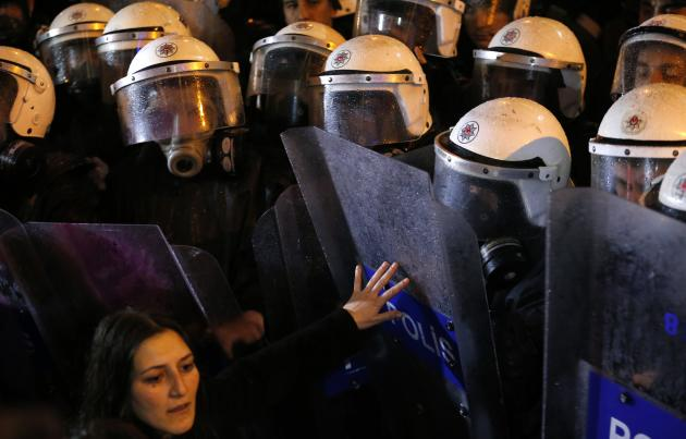 An activist for women's rights scuffles with riot police during an International Women's Day protest in Istanbul