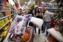 Target shoppers Kelly Foley, left, Debbie Winslow, center, and Ann Rich use a smartphone to look at a competitor's prices while shopping shortly after midnight on Black Friday, Nov. 28, 2014, in South Portland, Maine. (AP Photo/Robert F. Bukaty)