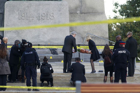 Canada's Prime Minister Harper and his wife lay flowers at the Canadian War Memorial in downtown Ottawa