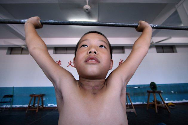 A Chinese boy practises weightlifting at a weightlifting training school in Jinjiang, in south China's Fujian province on July 22, 2011. Young Chinese athletes often enroll in sports schools in the ho