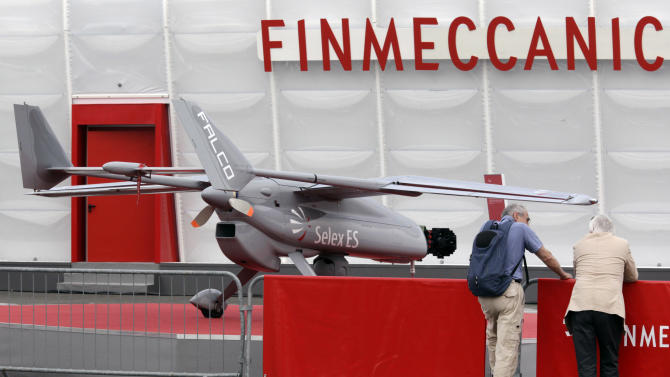 Two visitors, near a model version of a Falco aircraft, made by Finmeccanica, at the 50th Paris Air Show at Le Bourget airport, north of Paris,Tuesday June 18, 2013. (AP Photo/Remy de la Mauviniere)