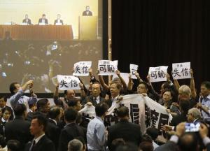 Pro-democracy lawmakers hold up a banner and signs during a protest as Li Fei (seen on screen), deputy general secretary of the National People's Congress (NPC) standing committee, speaks during a briefing session in Hong Kong