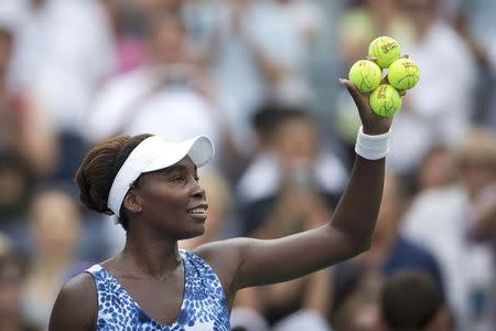 Williams of the U.S. holds signed tennis balls after defeating Puig of Puerto Rico at the U.S. Open Championships tennis tournament in New York