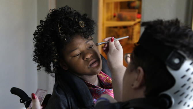 In this Nov. 14, 2012 photo, Carrie Ann Lucas, right, applies makeup for her daughter Adrianne, 13, at their home in Windsor, Colo., to prepare for a trip to an adoption hearing for her son, Anthony. (AP Photo/Brennan Linsley)