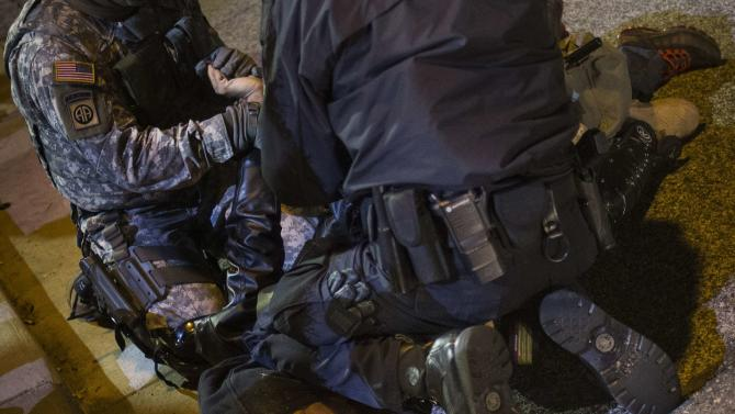 A policeman and member of the National Guard detain a man who was demanding justice for the killing of Brown, outside the Ferguson Police Department in Missouri