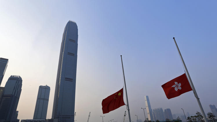 China's and Hong Kong's national flags fly at half-mast against Hong Kong's Victoria Habour Thursday, Oct. 4, 2012, as three days of mourning were to begin across the territory to mourn the victims who were killed in a ferry collision. Shock over Monday's crash, which left 38 dead, gave way to outrage Wednesday over what experts concluded was human error. (AP Photo/Vincent Yu)