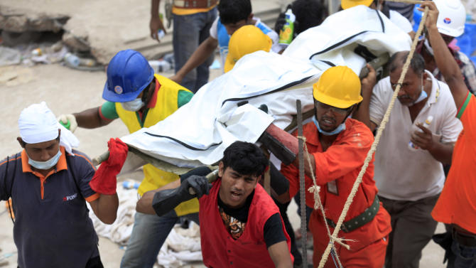 In this photo taken on Sunday April 28, 2013, volunteer workers bear with the stench from decomposing bodies as they transport them out of the disaster site. When the Rana Plaza, a garment factory building collapsed, many of the first responders were neighborhood residents, fellow garment workers, relatives of the missing and charity workers, and they repeatedly took some of the most dangerous work.(AP Photo/Wong Maye-E)