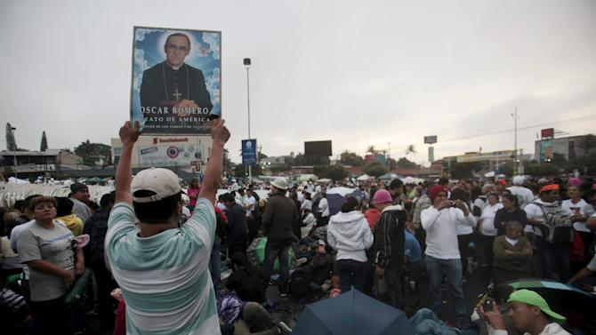 Catholic faithful holds a poster while waiting for the beatification ceremony for the late Archbishop of San Salvador Oscar Arnulfo Romero at El Salvador del Mundo square in San Salvador