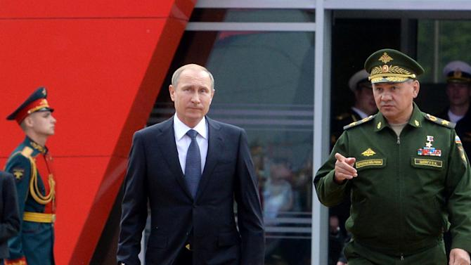 Russian President Vladimir Putin, center, and Defense Minister Sergei Shoigu, right, arrive for the opening of the Army-2015 international military show in Kubinka, outside Moscow, on Tuesday, June 16, 2015. The show features the latest Russian weapons. Putin said Tuesday the Russian military will receive 40 new intercontinental ballistic missiles this year capable of piercing any missile defenses, a blunt reminder of the nation's nuclear might amid tensions with the West over Ukraine. (Vasily Maximov/ pool photo via AP)