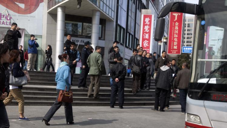 Plainclothes security personnel film as they gather to load detained worshippers onto a waiting bus near a building that leaders of the unregistered Shouwang house church had told parishioners to gather in Beijing, China, Sunday, April 10, 2011.  Beijing police on Sunday detained at least a dozen worshippers from the Christian house church who were trying to hold services in a public space after they were evicted from their usual place of worship. (AP Photo/Ng Han Guan)
