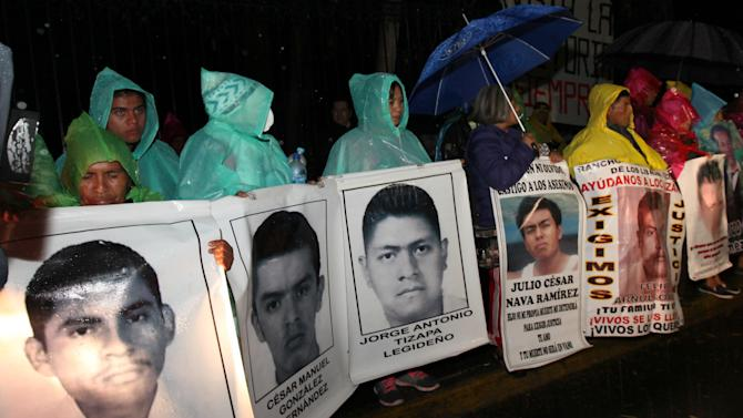 The relatives of 43 missing college students hold posters with images of their missing loved ones, as they protest their disappearance, at the Los Pinos presidential residence in Mexico City, Wednesday, Dec. 24, 2014. The relatives of the missing students called for peaceful demonstrations to pressure the government to find the truth about the missing students. The students went missing Sept. 26 after confrontations with police in Iguala, in southern Guerrero state, that killed three students and three bystanders. (AP Photo/Marco Ugarte)