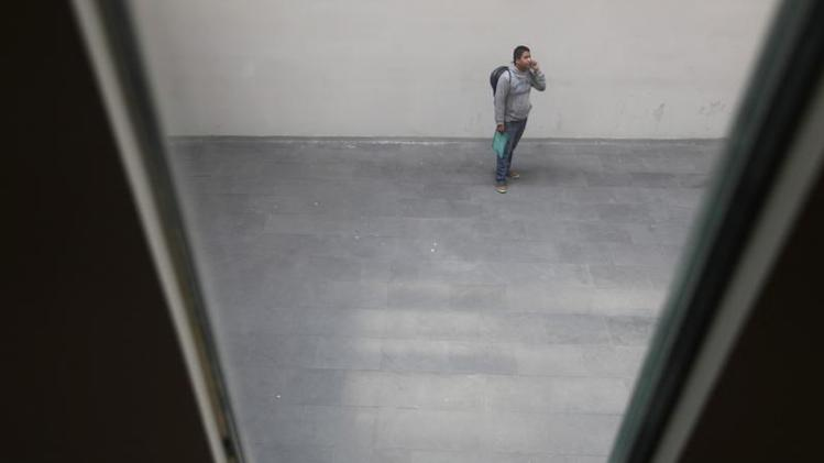 An applicant speaks on his mobile phone before a selection process for entry into the school of Maricahi Ollin Yoliztli in Mexico City