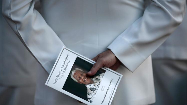 An officer of the armed forces of Brazil holds a picture of former South African President Nelson Mandela during a mass in honor of him in Brasilia