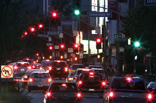 In this April 25, 2013 photo, stoplights and traffic are seen on Wilshire Boulevard in Los Angeles. The nation's most congested city has become a model for traffic control. With the flip of a switch e