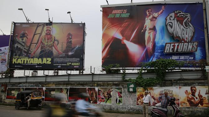 Commuters move past posters and hoardings of Indian films in Mumbai, India, Tuesday, Aug 19, 2014. Police say they have arrested the head of India's film censorship board for allegedly taking bribes in exchange for speeding up the approval of a film.(AP Photo/Rafiq Maqbool)