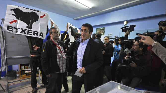 "Basque Regional President or ""Lehendakari"", Patxi Lopez, center, arrives to vote, in Bilbao, northern Spain, Sunday Oct. 21, 2012, as pro-independence demonstrators display flags calling to return all prisoners of the Basque armed group ETA to the Basque Country. Almost 4.5 million people will go to the polls Sunday in regional elections in Spain's turbulent Basque region and in northwestern Galicia. (AP Photo/Alvaro Barrientos)"