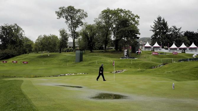 A staff member checks the green during a rain delay in the first round of the Evian Championship women's golf tournament in Evian, eastern France, Thursday, Sept. 12, 2013. (AP Photo/Laurent Cipriani)