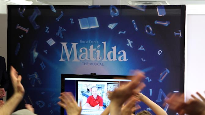 """This May 7, 2013 photo shows the cast of the Tony Award-nominated """"Matilda"""" waving to Tim Marshburn, one of six astronauts aboard the International Space Station, via a satellite hook-up provided by NASA, at a gathering in New York. Cast members, including many children, packed a small room near Times Square on Tuesday to ask questions about life in space.  (AP Photo/Mark Kennedy)"""