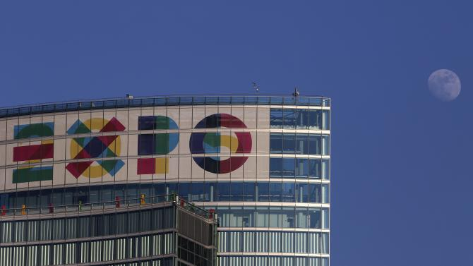 The moon is seen above the logo of the Expo Milano 2015, on top of the new headquarters of the Lombardia Region in downtown Milan