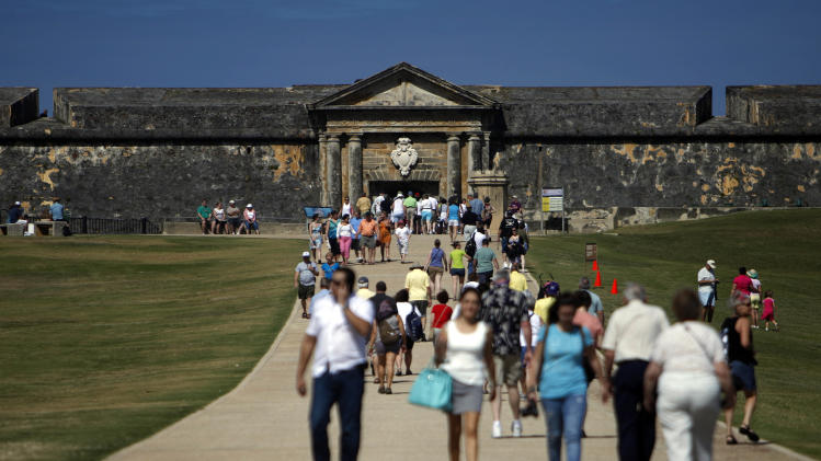 "Tourists walk near the 16th century Spanish fort called El Morro in Old San Juan, Puerto Rico, Jan. 24, 2013. There's an entrance fee to enter the Castillo San Felipe del Morro, but the best way to enjoy this U.S. National Historic Site requires no money at all. The fort that towers over San Juan Bay, known universally as just ""El Morro,"" is a great place to stroll, especially at sunset. The massive rolling expanse of grass at the foot of the fort has spectacular views in any direction. It's a popular place to picnic and fly a kite, sold by nearby street vendors. (AP Photo/Ricardo Arduengo)"
