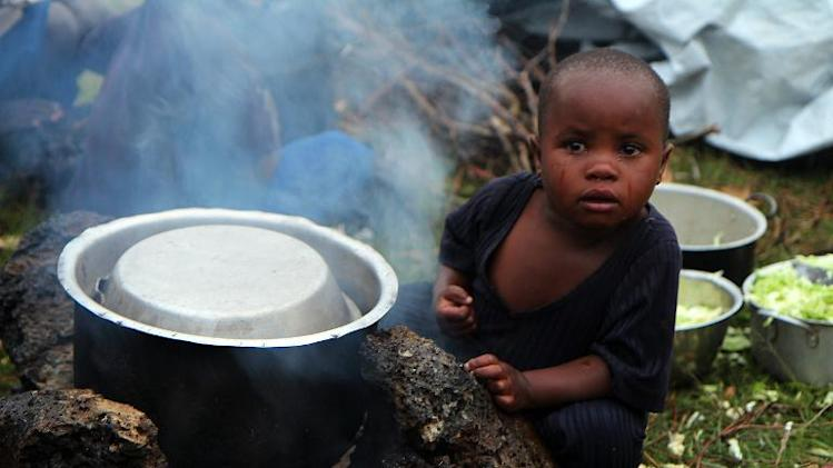 A boy tries to stay warm near a fire as refugees from the Democratic Republic of Congo fleeing fightings between the Congolese army and M23 rebels gather on the border in Bunagana on November 2, 2013