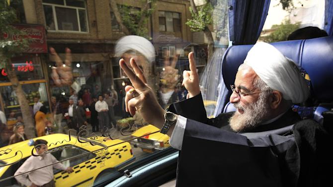 """In this Monday, June 10, 2013 photo, Iranian President elect, Hasan Rouhani, a former Iran's top nuclear negotiator, waves, from his bus, during his presidential election campaign tour to the western city of Sanandaj, Iran. Just a week before Iran's election gatekeepers announced the presidential ballot, Rouhani described the U.S. as the world's """"sheriff"""" and said direct talks with Washington are the only way for breakthroughs in the nuclear standoff. (AP Photo/Vahid Salemi)"""