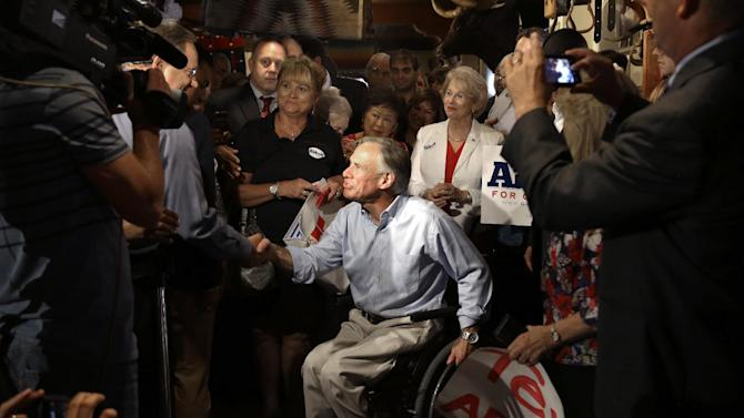 FILE - In this July 15, 2013 file photo,Texas Attorney General and Republican gubernatorial candidate Greg Abbott is welcomed by supporters during an appearance in Houston. At 26, Abbott lost the use of both legs when a 75-foot oak tree fell on him. Abbott is the early favorite in next year's race to succeed Gov. Rick Perry, who is not seeking another term. If Abbott wins, he would become the nation's first elected governor in a wheelchair since Franklin D. Roosevelt won New York in 1929. (AP Photo/Pat Sullivan, File)