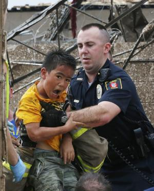FILE- In this May 20, 2013 file photo, Kai Heuangpraseuth is pulled from beneath a collapsed wall at the Plaza Towers Elementary School following a tornado in Moore, Okla. Heuangpraseuth will return to a new Plaza Towers Elementary in the fall, built on the same spot where seven of his schoolmates died last year during the storm. (AP Photo Sue Ogrocki, File)
