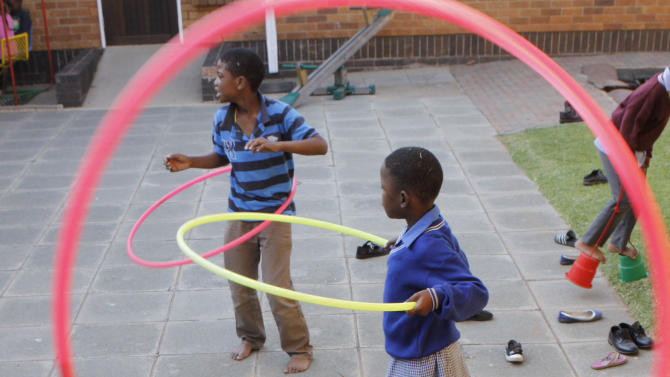In this photo taken Wednesday, May 8, 2013 children play with hula hoops during play time at Cotlands, a local non-profit organization that promotes early learning opportunities for children, in Johannesburg. Cotlands first opened it's doors 77 years ago offering adoption services for abandoned babies. In 1996 it opened an HIV hospice to address the increased HIV birth rate which claimed 98 children in 2002. In the past three years no child has died leading to the closure of the HIV hospice and now prioritizes it's efforts into advocation for an improvement in early childhood education. (AP Photo/Denis Farrell)