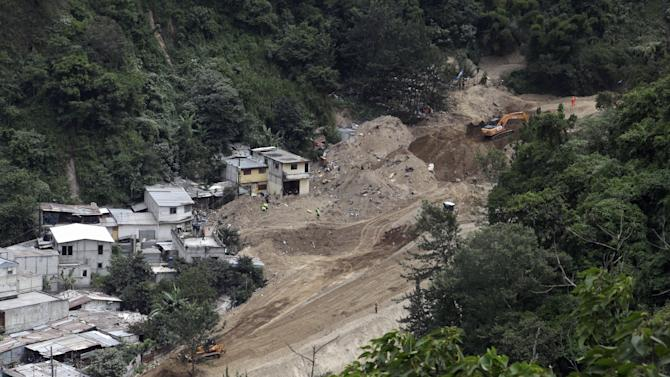 A general view shows heavy machinery and rescue team members working at an area affected by a mudslide in Santa Catarina Pinula