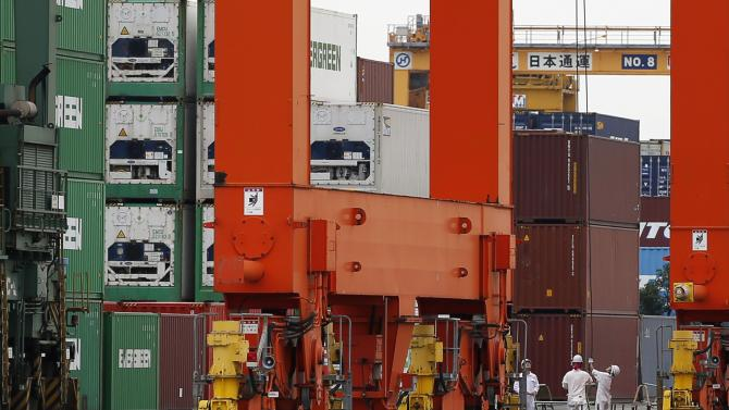 Workers are seen in a container area at a port in Tokyo