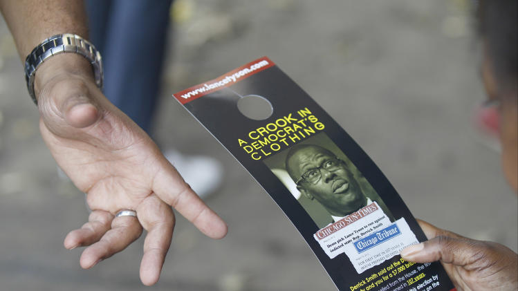 "In this Oct. 24, 2012 photo, while campaigning in Chicago, Unity Party candidate Lance Tyson, points to his campaign literature against against Derrick Smith, a former state representative indicted on federal bribery charges - and on the ballot as a Democrat - who is fighting to regain Illinois' 10th legislative district seat he was expelled from in August. A victory for Smith could be another embarrassment for a party and a state that already have a reputation for corruption, party leaders say, and they are going to great lengths to defeat Smith. The district's Democratic party committeemen announced a new political party called the ""10th District Unity Party"" and selected Tyson to take on Smith. (AP Photo/Charles Rex Arbogast)"