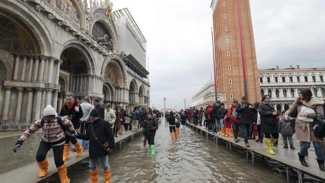 Tourists walk on raised platforms above flood waters during a period of seasonal high water and the first day of carnival in Venice