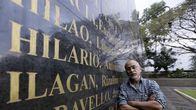 Filipino poet Bonifacio Ilagan, one of hundreds of activists imprisoned during the Martial Law period which was declared by the late strongman Ferdinand Marcos, poses by the granite wall which is engraved with the names of Martial Law victims, including his sister Rizalina Ilagan, at the Heroes Shrine at suburban Quezon city, northeast of Manila, Philippines Monday Jan. 28, 2013. More than 9,000 victims will be awarded compensation using $246 million that the Philippine government recovered from Marcos' ill-gotten wealth. But all claims will still have to evaluated by an independent commission and the amount each will receive will depend of the abuse suffered. (AP Photo/Bullit Marquez)