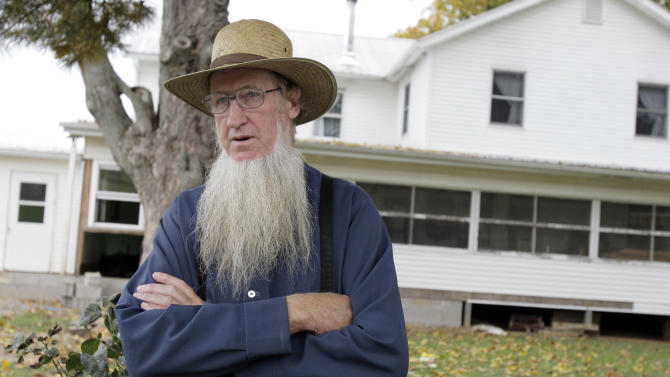 FILE - In this Monday, Oct. 10, 2011 file photo, Sam Mullet stands in front of his Bergholz, Ohio, home. An appeals court on Wednesday, Aug. 27, 2014 overturned the hate-crime convictions of 16 Amish in beard- and hair-cutting attacks on fellow members of their faith in Ohio. The 6th U.S. Circuit Court of Appeals in Cincinnati sided with arguments brought by attorneys for the Amish, who were convicted two years ago in five attacks in Ohio Amish communities in 2011. The attacks were in apparent retaliation against Amish who had defied or denounced the authoritarian style of leader Mullet. (AP Photo/Amy Sancetta, File)