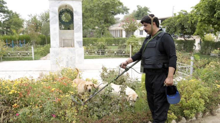 A member of the Pakistani police bomb squad demonstrates the workings of a technical equipment and explosive sniffing dogs which are used by police in Dera Ismail Khan