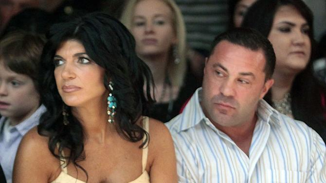 """FILE - This Sept. 13, 2009 file photo originally released by Oral-B Pulsonic shows """"Real Housewives of New Jersey"""" stars, Teresa Giudice, left, and her husband Joe Giudice at the Caravan Fashion Show sponsored by Oral-B Pulsonic in New York. Teresa and Giuseppe """"Joe"""" Giudice were charged in a 39-count indictment handed up Monday, July 29, 2013, in Newark, N.J. The two are accused of submitting fraudulent mortgage and other loan applications from 2001 through 2008, a year before their show debuted on Bravo. Prosecutors say they made false claims about their employment status and salaries. (AP Photo/Oral-B Pulsonic, Gary He)"""