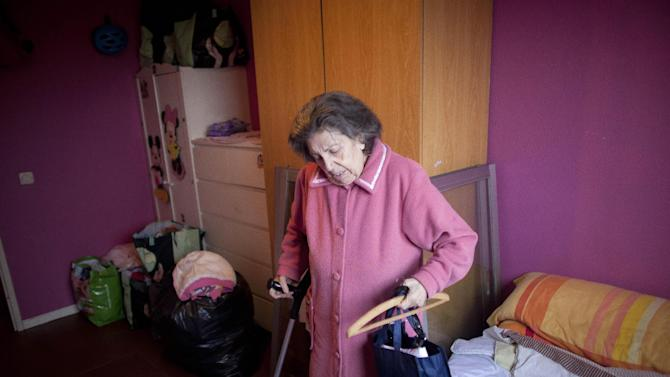 File - In this Nov. 18, 2011file photo, Azucena Paredes' grandmother Tomasa Morcillo, 87, picks up her personal belongings as she and her family are evicted from their home in Madrid. The Spanish government Thursday Nov. 15, 2012 passed a decree curbing evictions of lower income homeowners unable to pay their mortgage, a bid to ease a trend that has seen hundreds of thousands of people lose their homes because of the brutal economic crisis. The urgent measure stops evictions for two years of people whose unemployed benefits have expired or who have incomes of less than €1,200 ($1,527) a month after tax and whose mortgage represents at least 50 percent total household income. Public attention on the issue intensified greatly in recent weeks after two homeowners facing eviction committed suicide. Spaniards are also angry because while people lose their homes, the government is negotiation billion-dollar bailouts for the same banks who are repossessing the houses. Over the past four years, social groups have begun organizing street protests to try to avoid prevent court officials and police carrying out eviction orders.  (AP Photo/Arturo Rodriguez, File)