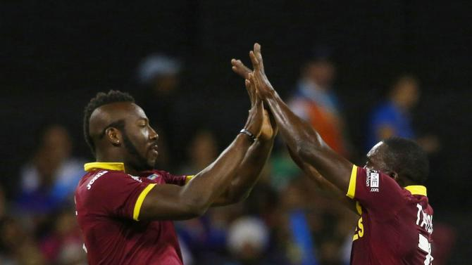 West Indies Andre Russell and Jerome Taylor leap into the air in celebration after India's Rohit Sharma was dismissed during their Cricket World Cup match in Perth