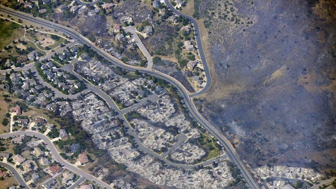 This aerial photo taken on Wednesday, June 27, 2012, shows burned homes in the Mountain Shadows residential area of Colorado Springs, Colo., that were destroyed by the Waldo Canyon wildfire. More than 30,000 have been displaced by the fire, including thousands who frantically packed up belongings Tuesday night after it barreled into neighborhoods in the foothills west and north of Colorado's second-largest city. (AP Photo/John Wark)